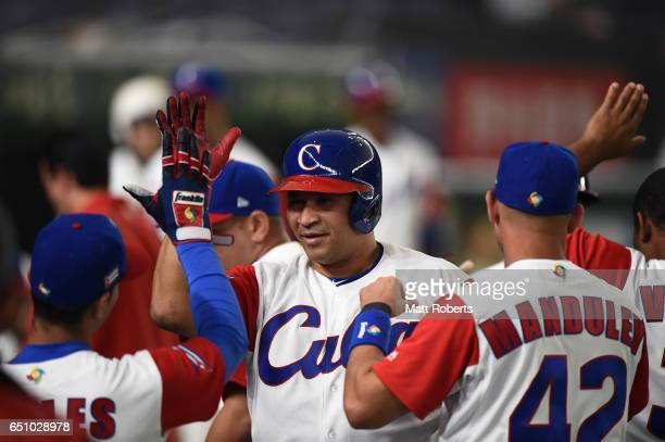 Outfielder Alfredo Despaigne of Cuba celebrates with his team mates after hitting a grand slam to make it 14 in the bottom of the fifth inning during...
