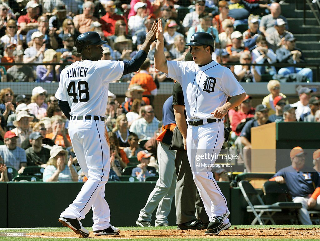 Outfielder Andy Dirks #12 of the Detroit Tigers celebrates with outfielder Torii Hunter #48 after scoring against the Houston Astros March 4, 2013 at Joker Marchant Stadium in Lakeland, Florida.