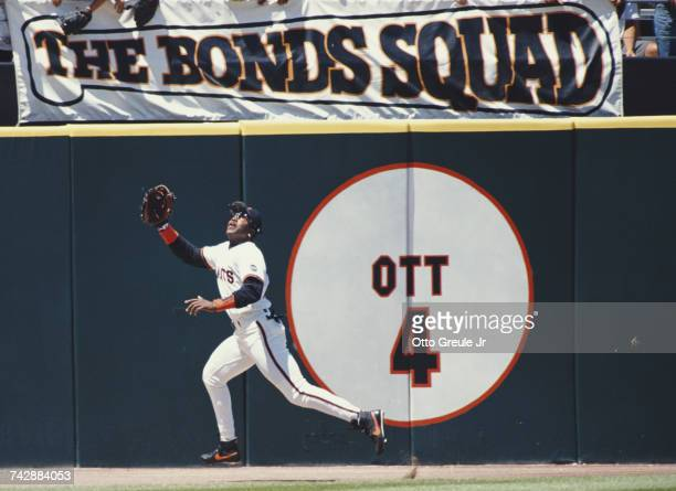 Outfielder Barry Bonds of the San Francisco Giants reaches for the ball beneath a Bonds Squad banner during the Major League Baseball National League...