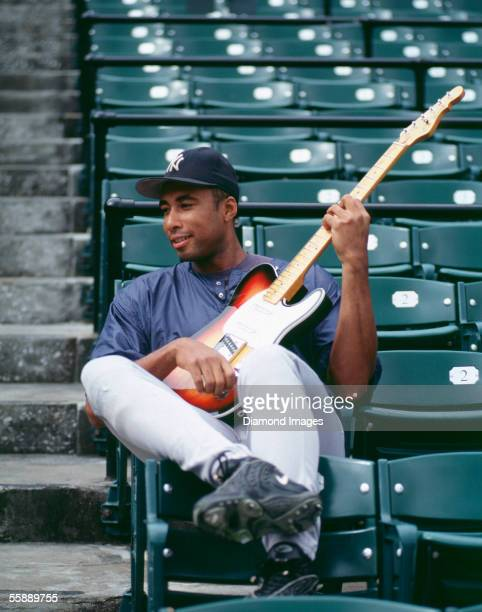 Outfielder Bernie Williams, of the New York Yankees, poses for a portrait with an electric guitar prior to a game against the Baltimore Orioles in...