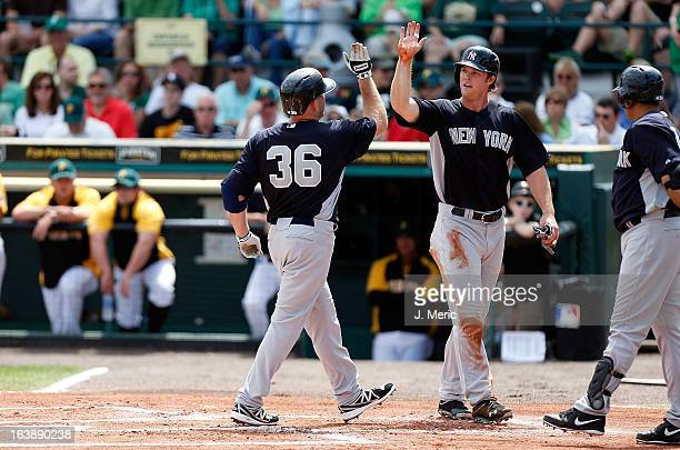 Outfielder Brennan Boesch of the New York Yankees congratulates Kevin Youkilis after his home run against the Pittsburgh Pirates during a Grapefruit...