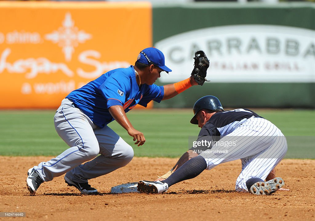 Outfielder Brett Gardner #11 of the New York Yankees dives into second base under a throw to infielder Ruben Tejada #11 of the New York Mets in a spring training game April 4, 2012 at George M. Steinbrenner Field in Tampa, Florida.