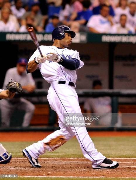 Outfielder Carl Crawford of the Tampa Bay Rays follows through on a grand slam home run against the Chicago Cubs June 19 2008 at Tropicana Field in...