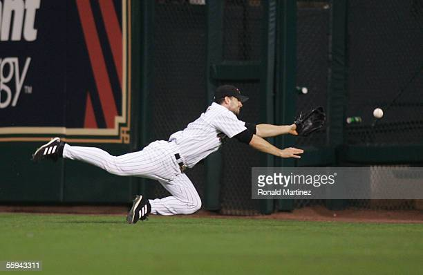 Outfielder Chris Burke of the Houston Astros makes a diving attempt at a double hit by Yadier Molina of the St Louis Cardinals during the second...