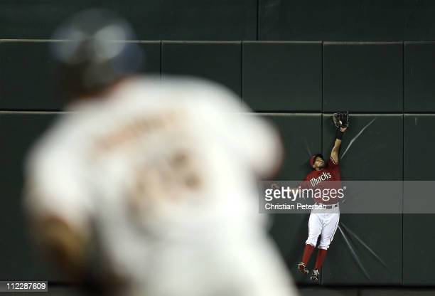 Outfielder Chris Young of the Arizona Diamondbacks makes a leaping catch on the fly ball hit by Pablo Sandoval of the San Francisco Giants during the...