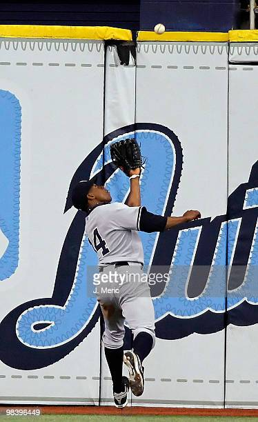 Outfielder Curtis Granderson of the New York Yankees catches a fly ball against the Tampa Bay Rays during the game at Tropicana Field on April 11...