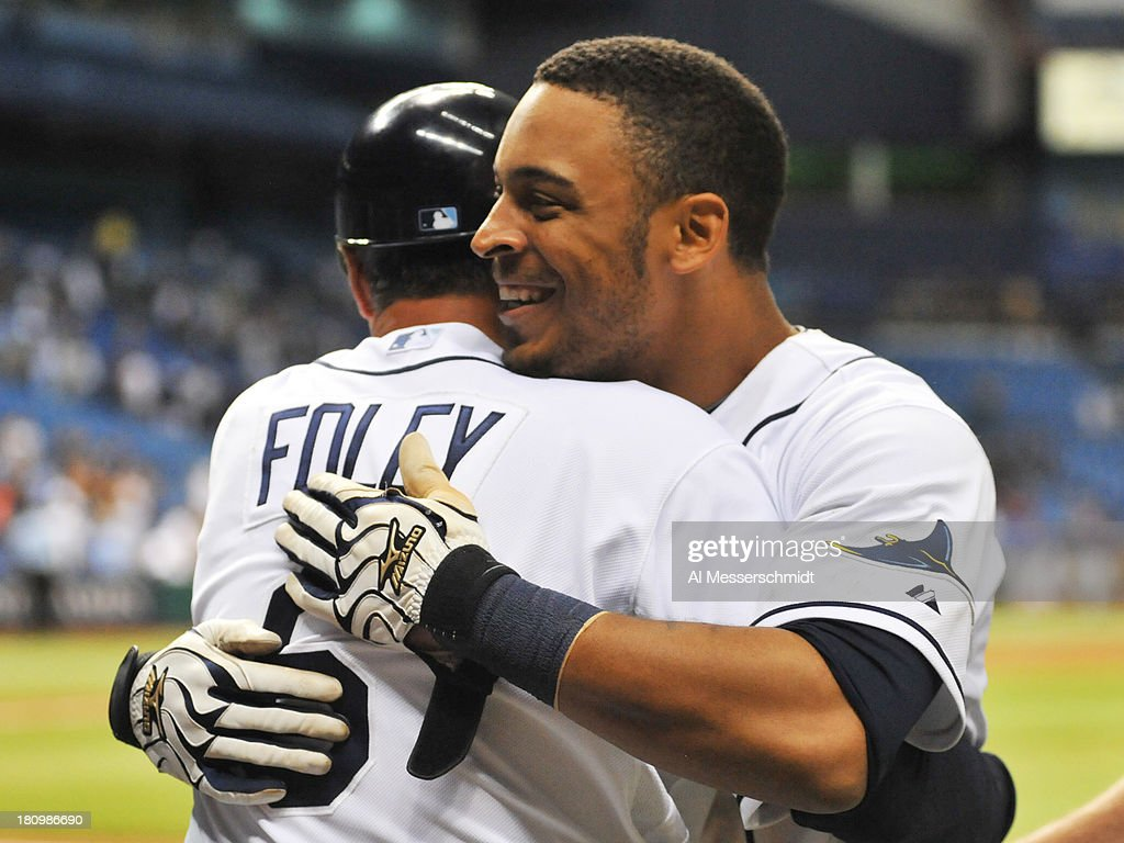 Outfielder Desmond Jennings #8 of the Tampa Bay Rays hugs 3rd base coach Tom Foley after driving in the winning run in the 12th inning against the Texas Rangers September 18, 2013 at Tropicana Field in St. Petersburg, Florida. The Rays won 4 - 3.