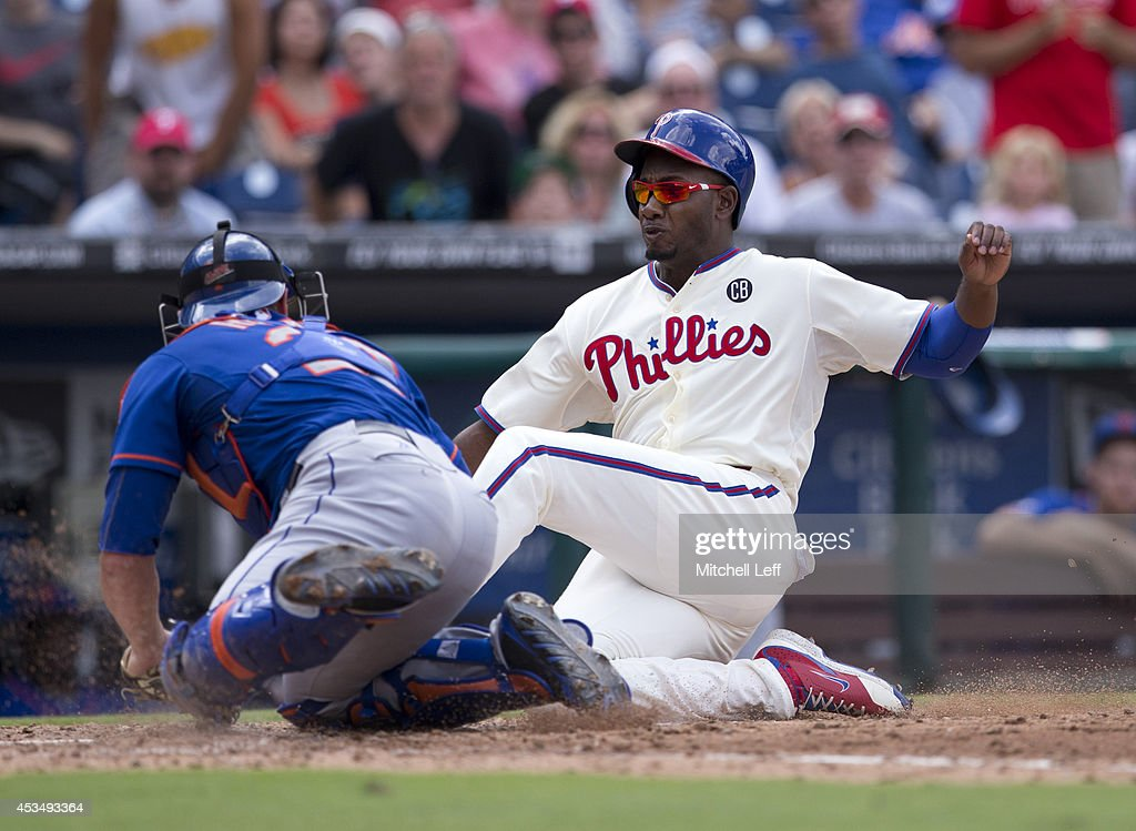 Outfielder Domonic Brown #9 of the Philadelphia Phillies is tagged out by catcher Anthony Recker #20 of the New York Mets in the bottom of the seventh inning on August 11, 2014 at Citizens Bank Park in Philadelphia, Pennsylvania.