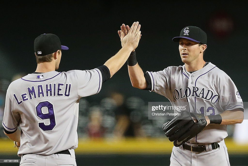 Outfielder Drew Stubbs #13 (R) of the Colorado Rockies high-fives DJ LeMahieu #9 after defeating the Arizona Diamondbacks in the MLB game at Chase Field on April 29, 2014 in Phoenix, Arizona. The Rockies defeated the Diamondbacks 5-4.