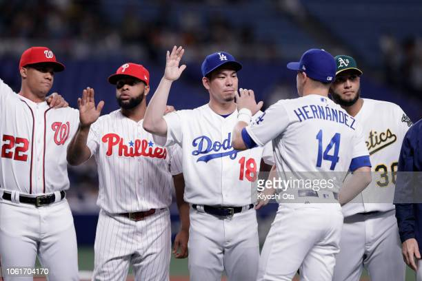 Outfielder Enrique Hernandez of the Los Angeles Dodgers high fives with his team mate Kenta Maeda as he is introduced prior to the game six between...