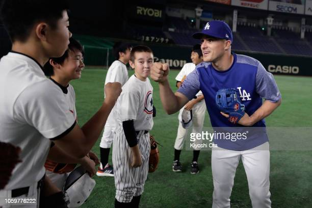 Outfielder Enrique Hernandez of the Los Angeles fist bumps with participants during the MLB Baseball Clinic prior to the game two of the Japan and...