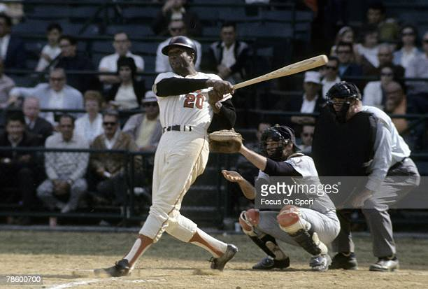 Outfielder Frank Robinson of the Baltimore Orioles swings and watches the flight of his ball during a circa late 1960s Major League Baseball game at...