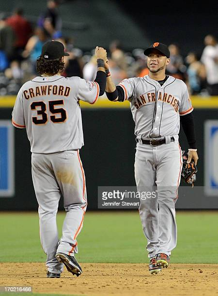 Outfielder Gregor Blanco and infielder Brandon Crawford of the San Francisco Giants celebrate on the field after defeating the Arizona Diamondbacks...