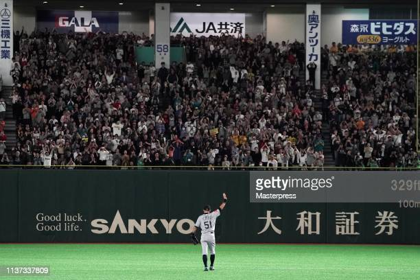 Outfielder Ichiro Suzuki of the Seattle Mariners applauds fans while he walks to the dugout as he is substituted to retire from baseball during the...