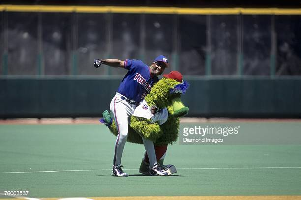 Outfielder Joe Carter of the Toronto Blue Jays throws a playful swing at the Philly Phanatic the mascot for the Philadelphia Phillies prior to a game...