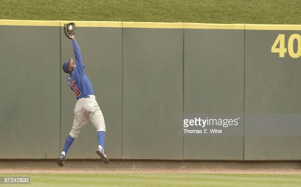 Outfielder Juan Pierre of the Chicago Cubs dives against the wall for the out against the Cincinnati Reds at Great American Ball Park on April 3,...