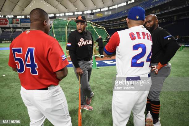 Outfielder Kalian Sams and Infielder Yurendell de Caster of the Netherlands talk with Outfielder Alfredo Despaigne and Designated hitter Frederich...