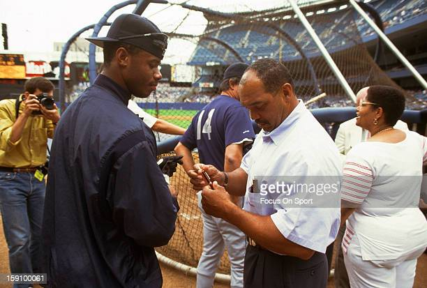 Outfielder Ken Griffey Jr #24 of the Seattle Mariners talks with former New York Yankee Reggie Jackson during batting practice before an Major League...