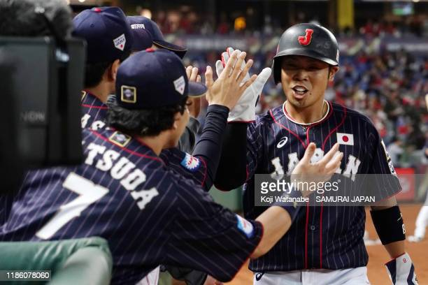 Outfielder Kensuke Kondo of Japan high fives with his team mates after scoring a run by the RBI triple of Outfielder Seiya Suzuki in the top of 1st...