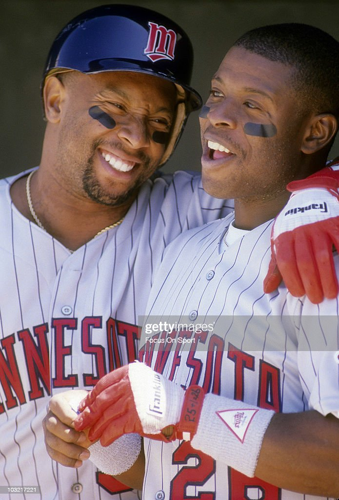 Outfielder Kirby Puckett #34 of the Minnesota Twins smiling with his arm around teammate Al Newman #26 in the dougout circa 1992 during a MLB baseball game. Puckett played for the Twins from 1984-95.