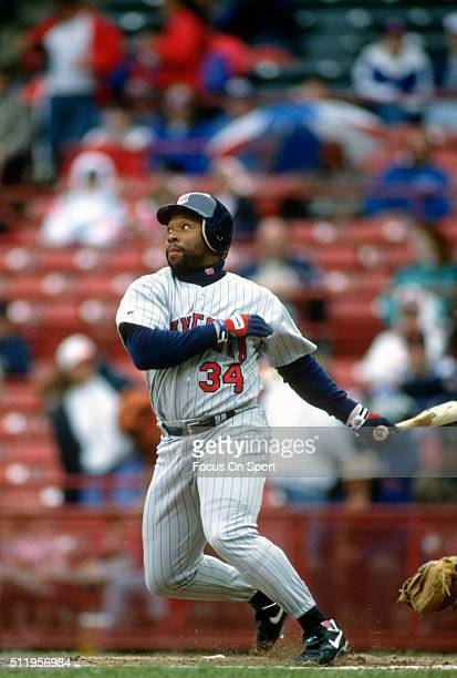 Outfielder Kirby Puckett of the Minnesota Twins swings and watches the flight of his ball against the Milwaukee Brewers during a Major League...