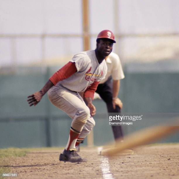 Outfielder Lou Brock of the St Louis Cardinals leads off third base during a Spring Training game against the New York Mets in March 1968 in St...