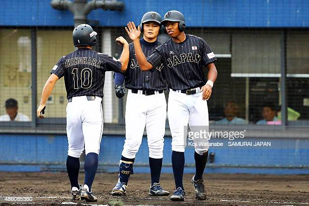 Outfielder Louis Okoye and Infielder Kotaro Kiyomiya of Japan celebrates after in the top half of the first inning in the first round game between...