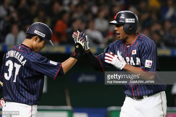 Outfielder Louis Okoye of Japan high fives with his team mate Outfielder Masayuki Kuwahara after scoring a run by the RBI double of Infielder Shuta...