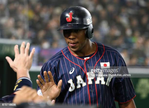 Outfielder Louis Okoye of Japan high fives with his team mates after scoring a run by the RBI double of Infielder Shuta Tonosaki to make it 8-0 in...