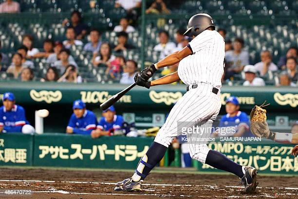 Outfielder Louis Okoye of Japan hits a single in the bottom half of the second inning the game between Australia and Japan in the super round game...