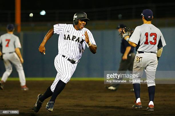 Outfielder Louis Okoye of Japan slides to third base in the bottom half of the fifth inning in the first round game between Japan and USA during the...