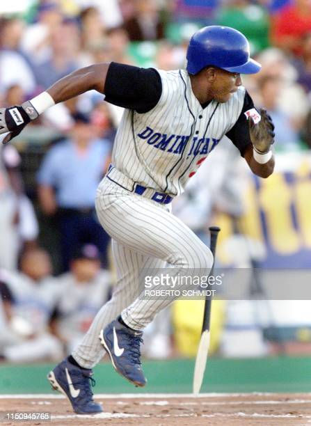 Outfielder Manny Martinez for the Tigres del Licey baseball team of the Dominican Republic runs to first base after breaking his bat in the game...