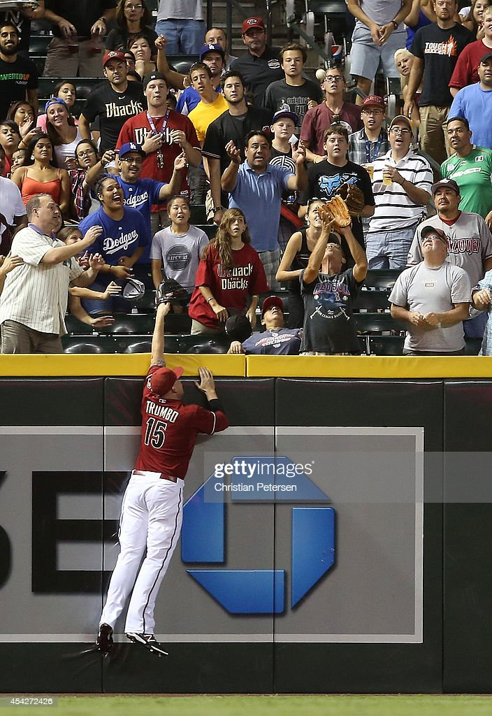 Outfielder Mark Trumbo #15 of the Arizona Diamondbacks leaps as he attempts to catch a home-run hit by Scott Van Slyke (not pictured) of the Los Angeles Dodgers during the third inning of the MLB game at Chase Field on August 27, 2014 in Phoenix, Arizona.
