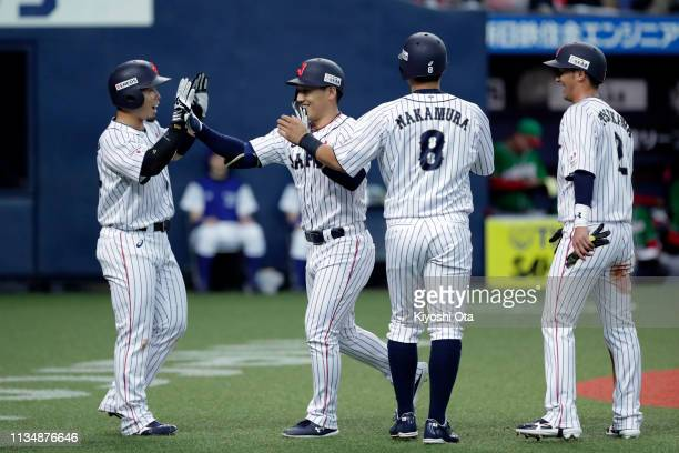 Outfielder Masataka Yoshida of Japan is congratulated by his team mates after hitting a grand slam to make it 04 in the bottom of 1st inning during...