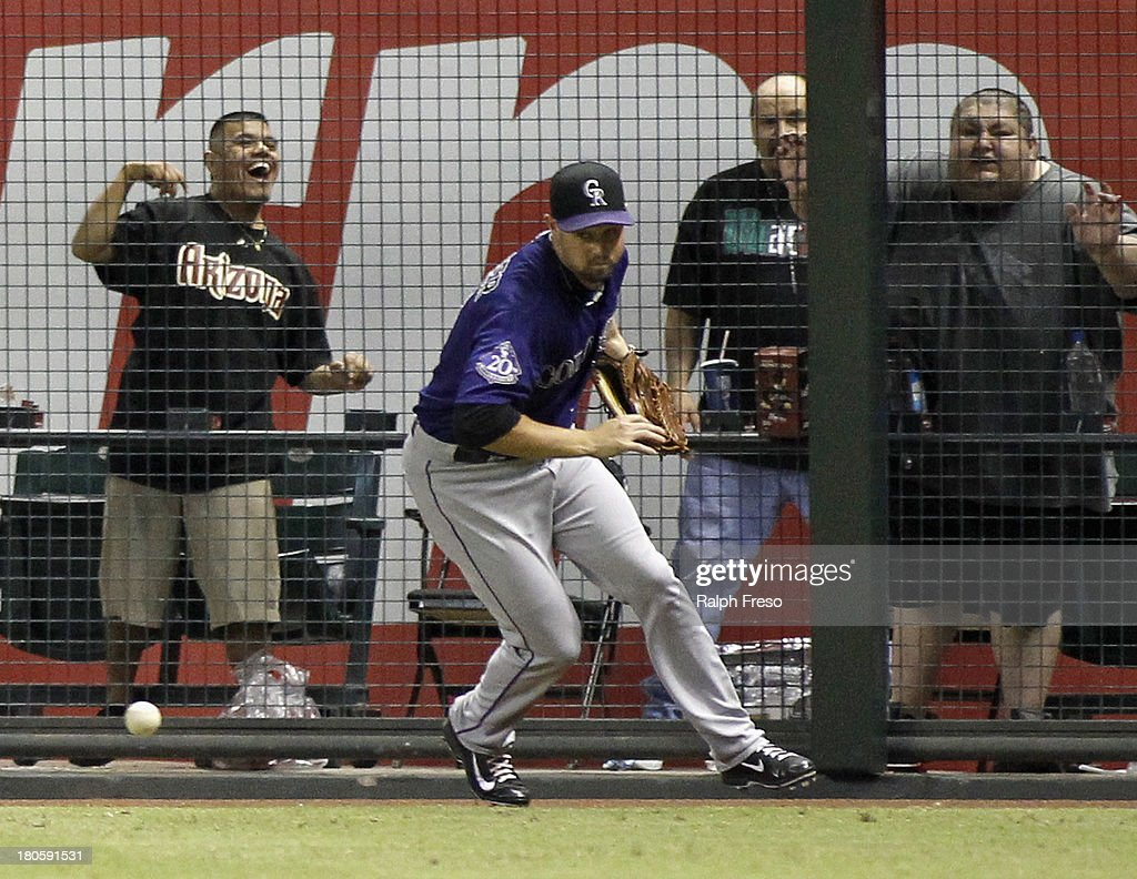 Outfielder Michael Cuddyer #3 of the Colorado Rockies has the ball bounce away from him on a triple by Paul Goldschmidt #44 of the Arizona Diamondbacks during the seventh inning of a MLB game at Chase Field on September 14, 2013 in Phoenix, Arizona.
