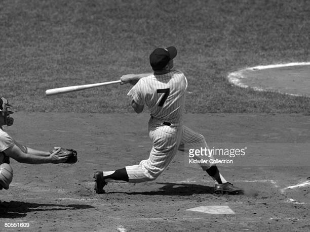 Outfielder Mickey Mantle of the New York Yankees swings at a pitch during a game in 1956 against the Chicago White Sox at Yankee Stadium in New York...