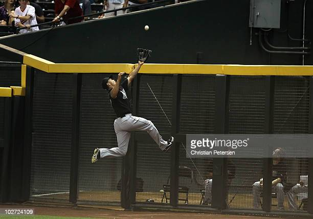 Outfielder Mike Stanton of the Florida Marlins leaps as he attempts to catch a 2 RBI triple hit by Kelly Johnson of the Arizona Diamondbacks during...