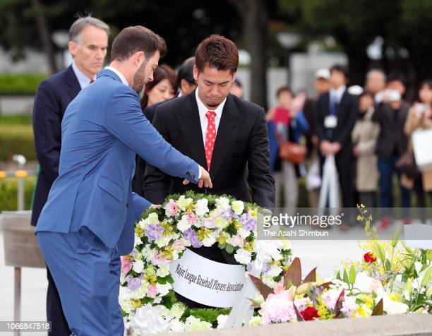 Outfielder Mitch Haniger of the Seattle Mariners and pitcher Kenta Maeda of the Los Angeles Dodgers offer a wreath at the cenotaph at the Hiroshima...