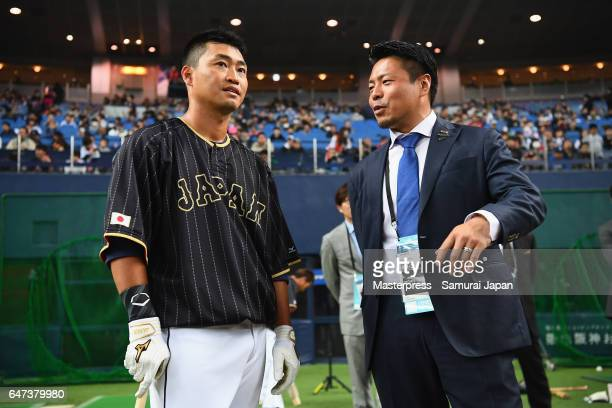 Outfielder Norichika Aoki of Japan talks with Akinori Iwamura prior to the World Baseball Classic WarmUp Game between Japan and Hanshin Tigers at...