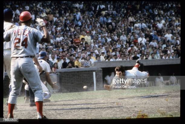 Outfielder Pete Rose of the Cincinnati Reds slides head first at home plate against the Chicago Cubs during a MLB baseball game circa late 1960s at...