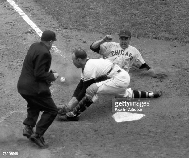 Outfielder Ralph Kiner of the Chicago Cubs slides home safely as catcher Wes Westrum of the New York Giants receives the throw too late from...