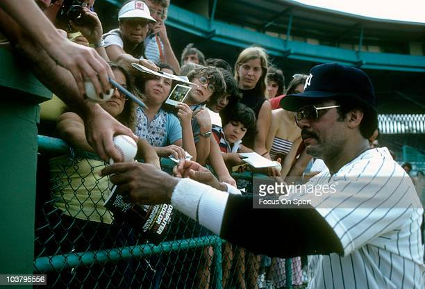 Outfielder Reggie Jackson of the New York Yankees signs autographs for fans during a spring training Major League baseball game circa 1980 in Tampa...