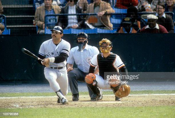 Outfielder Reggie Jackson of the New York Yankees swings and watches the flight of his ball against the Baltimore Orioles during a Major League...
