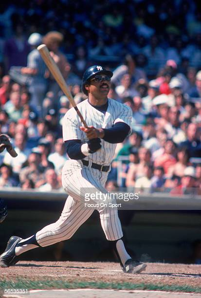 Outfielder Reggie Jackson of the New York Yankees swings and watches the flight of his ball during a game at Yankee Stadium circa the 1970's in Bronx...