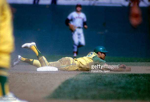 Outfielder Reggie Jackson of the Oakland Athletics slides into second base during a Major League Baseball game circa 1970 Jackson played for the...