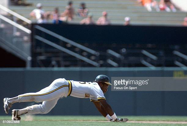 Outfielder Rickey Henderson of the Oakland Athletics dives back into second base against the Baltimore Orioles during an Major League Baseball game...
