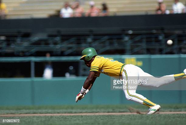 Outfielder Rickey Henderson of the Oakland Athletics dives into second base against the Baltimore Orioles during an Major League Baseball game circa...