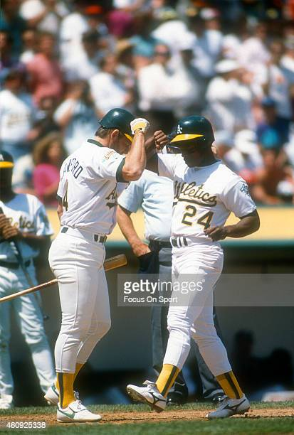 Outfielder Rickey Henderson of the Oakland Athletics is congratulated by Carney Lansford after Henderson hit a home run during an Major League...