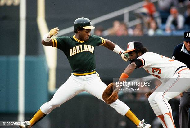 Outfielder Rickey Henderson of the Oakland Athletics jumps back safe at first base as the throw comes over to Eddie Murray of the Baltimore Orioles...