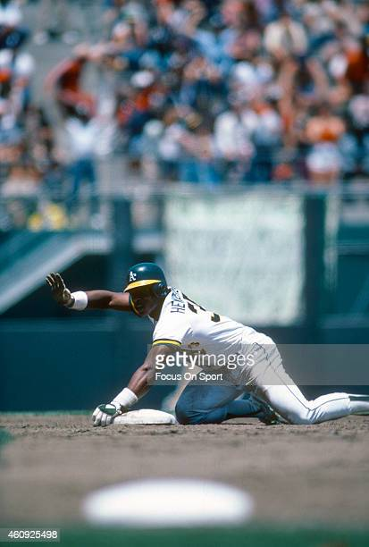 Outfielder Rickey Henderson of the Oakland Athletics steals second base and ask for timeout during an Major League Baseball game circa 1982 at the...